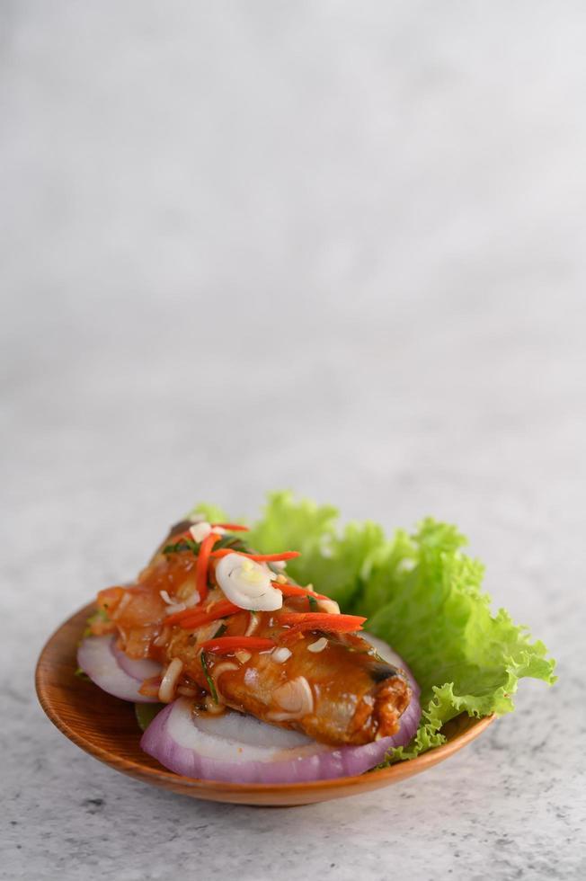 insalata di sardine piccanti in una ciotola di legno foto