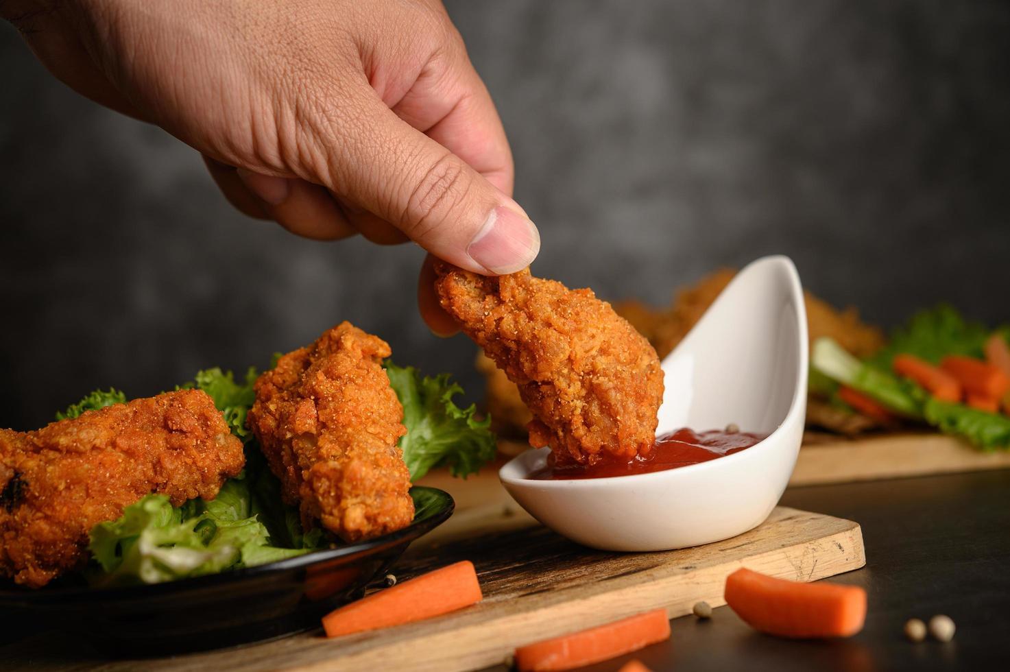 mano che immerge il pollo fritto croccante nella salsa foto