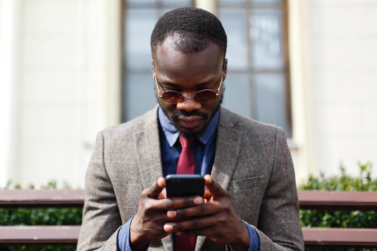 uomo che indossa occhiali da sole sta lavorando sul suo telefono foto