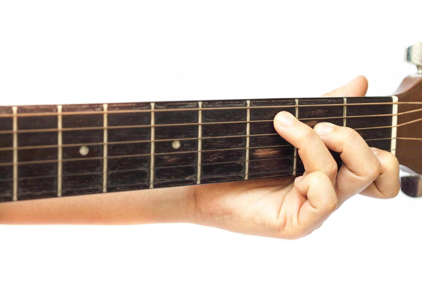 primo piano delle dita sul collo di una chitarra foto