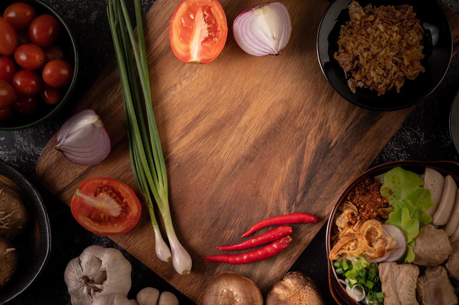scalogno, peperoni, aglio e funghi shiitake su una tavola di legno foto