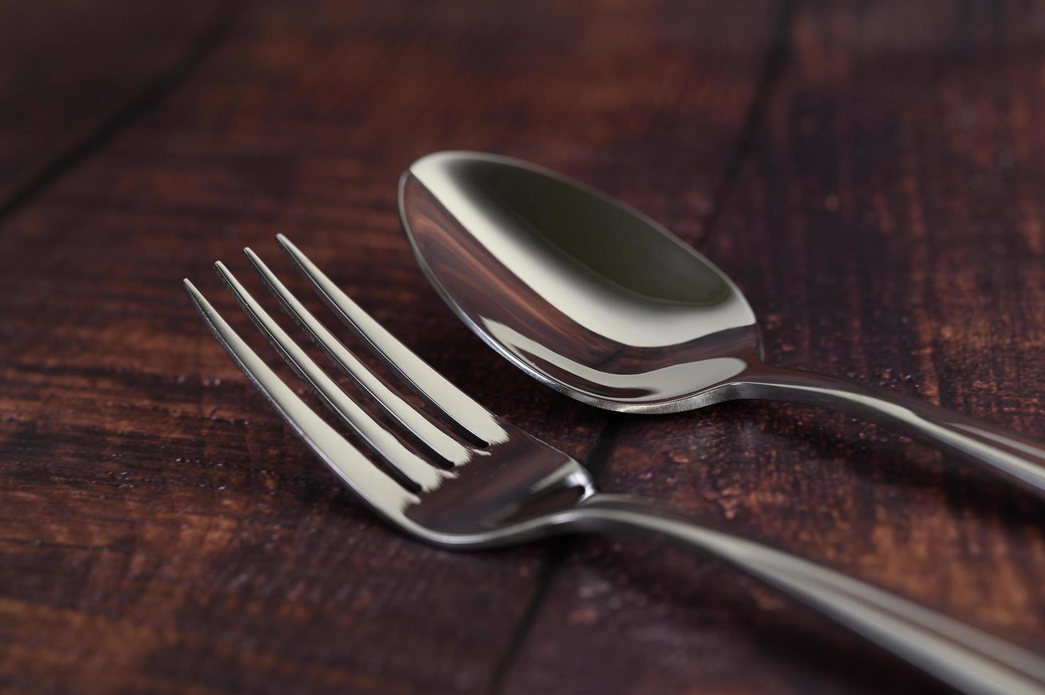 forchetta e cucchiaio in acciaio inox su un tavolo di legno foto