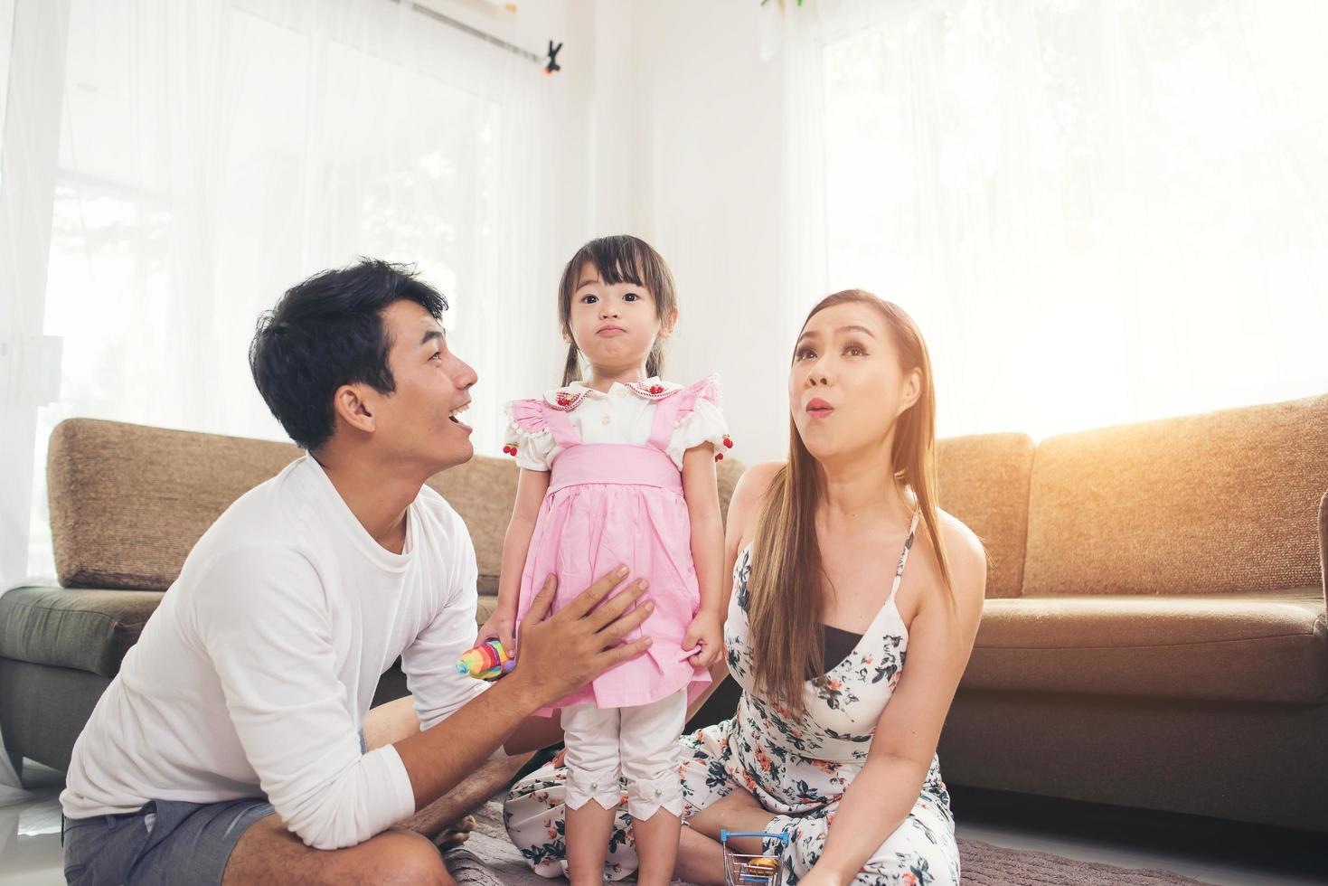 bambino con i suoi genitori che giocano sul pavimento a casa foto