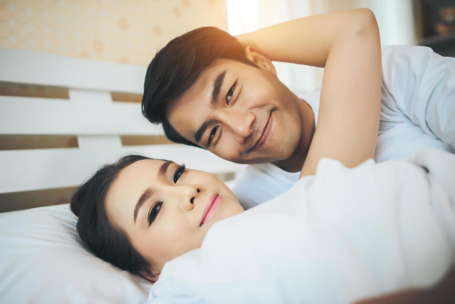 coppia felice posa insieme nel loro letto foto