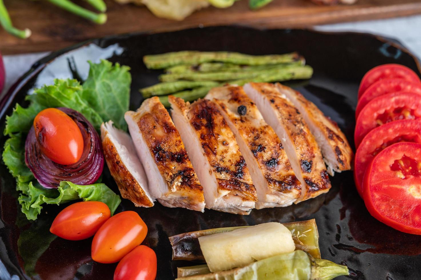 bistecca di pollo con insalata di verdure su un piatto nero foto