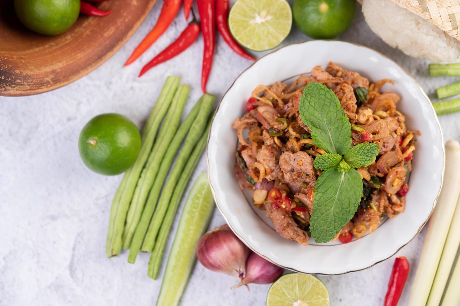 un piatto di carne di maiale tritata con gli ingredienti foto