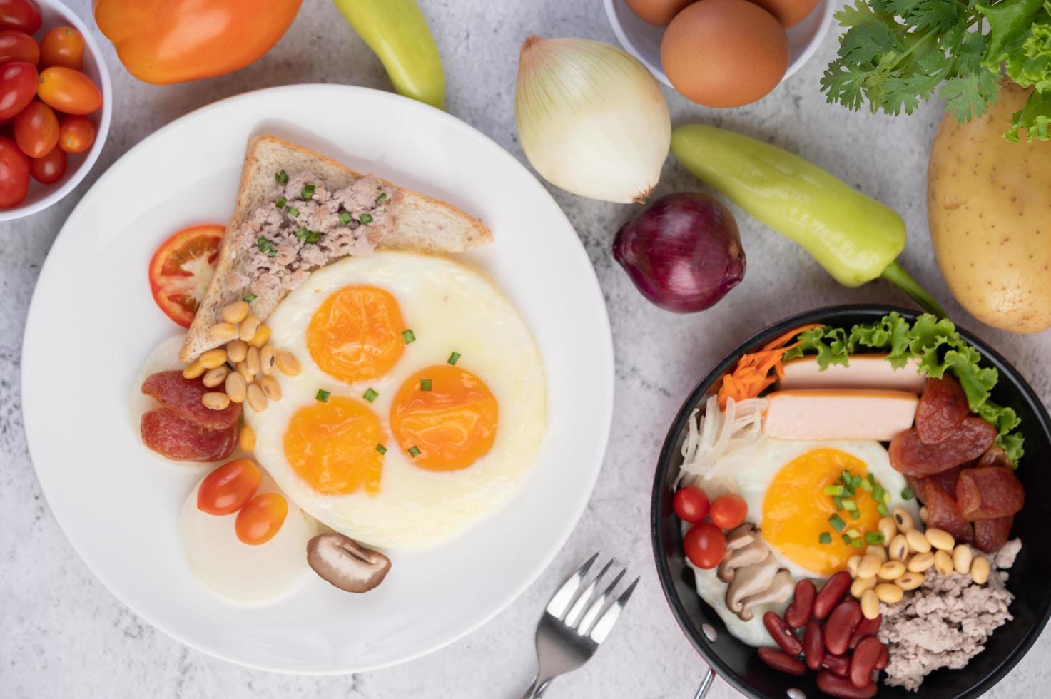 uova fritte, salsiccia, carne di maiale tritata, pane e fagioli rossi foto