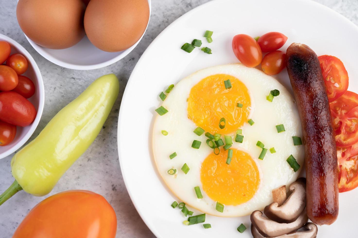 piatto della colazione con uova fritte, pomodori, salsiccia cinese e funghi foto