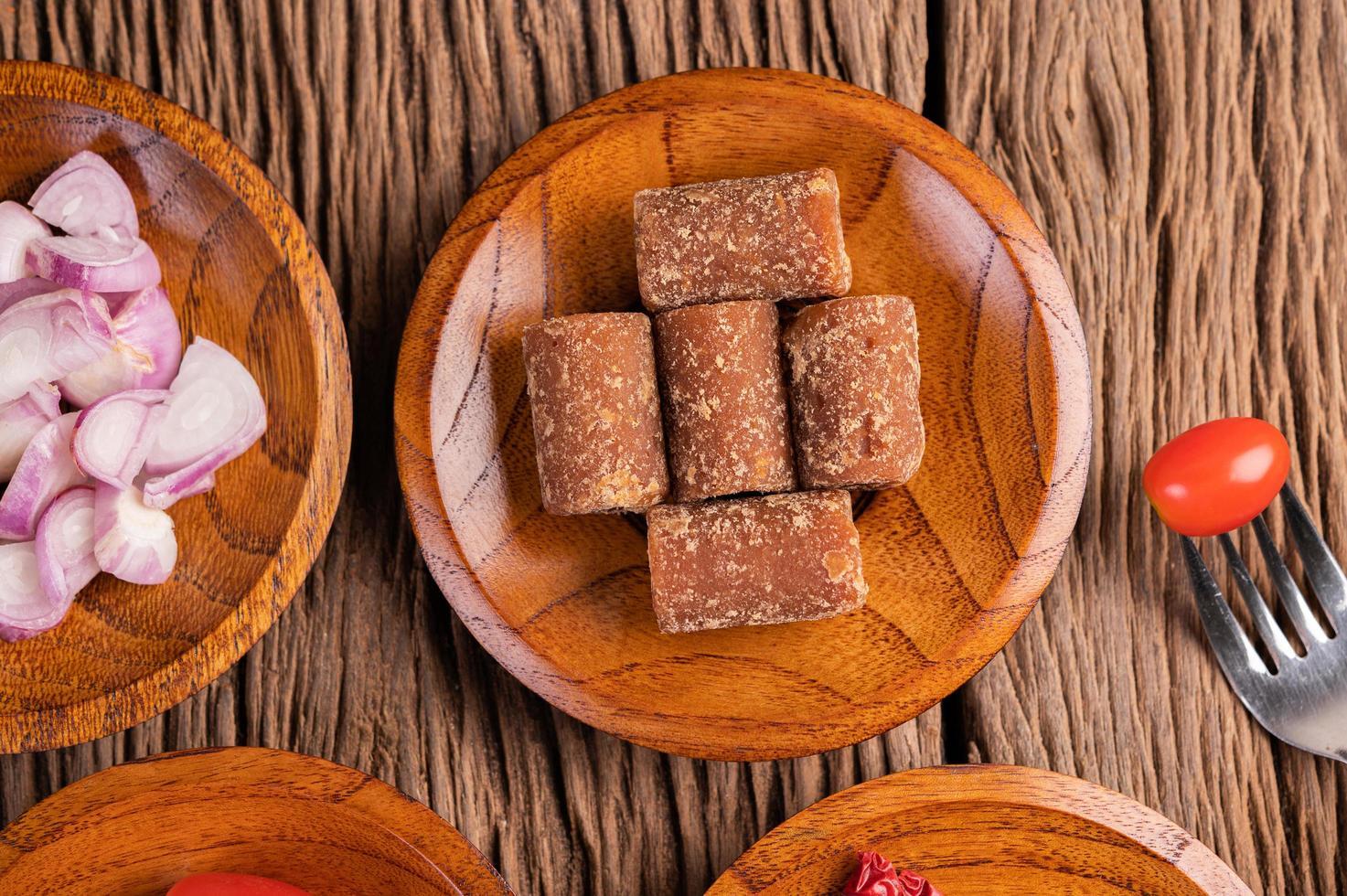 zucchero di palma e cipolle rosse su un piatto di legno foto