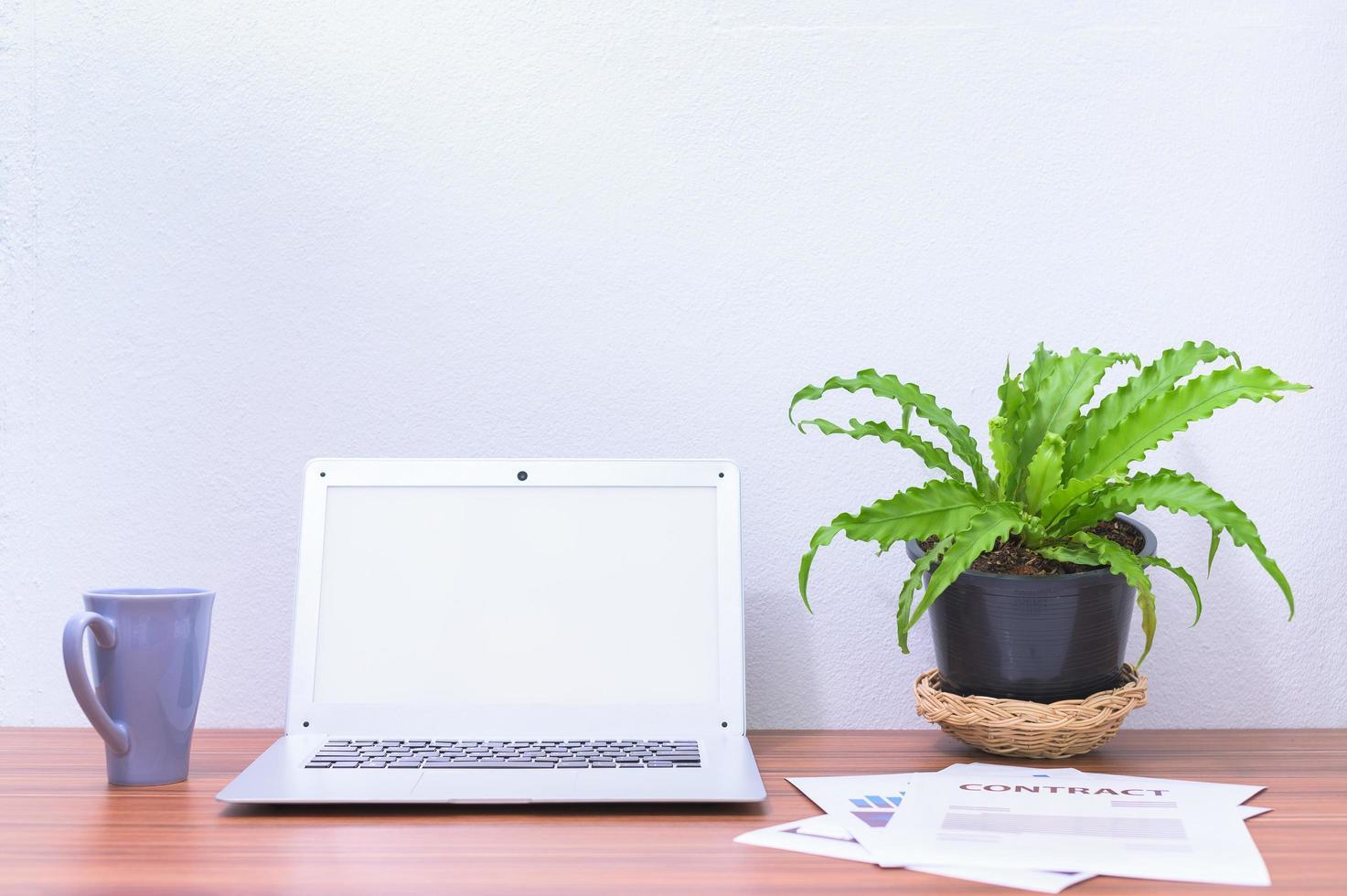 computer portatile e fiore sulla scrivania foto
