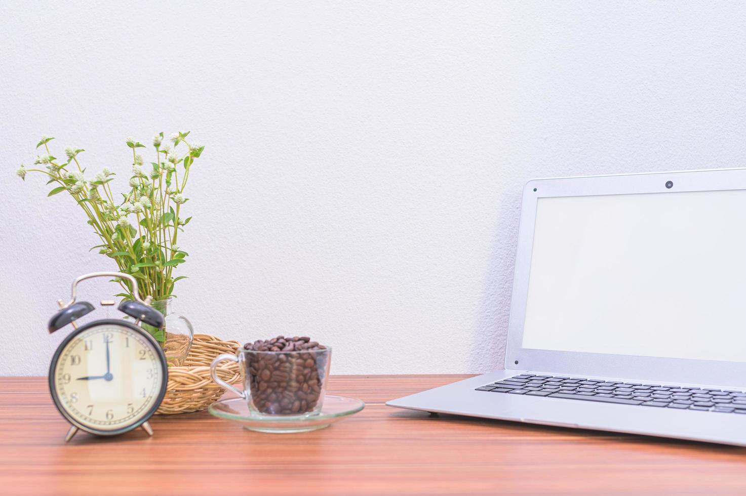 laptop e fiore sulla scrivania foto