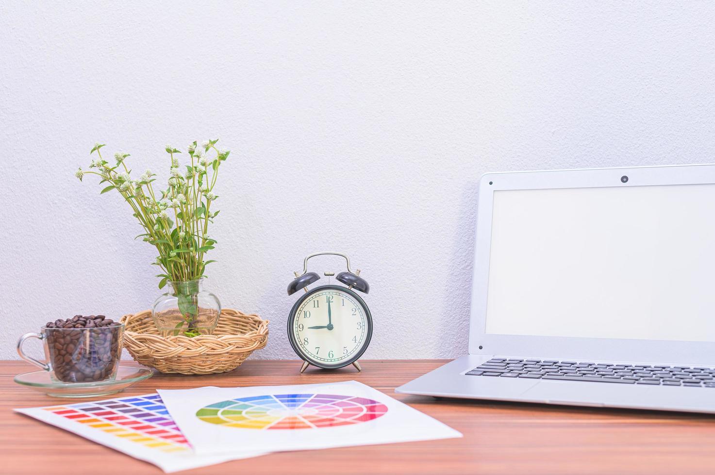 laptop, documenti e fiori sulla scrivania foto