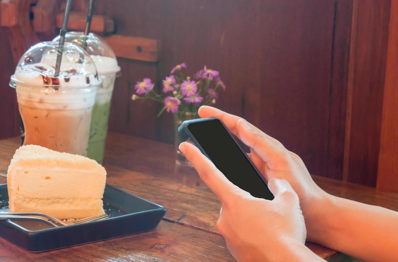 persona che utilizza un telefono in una caffetteria foto