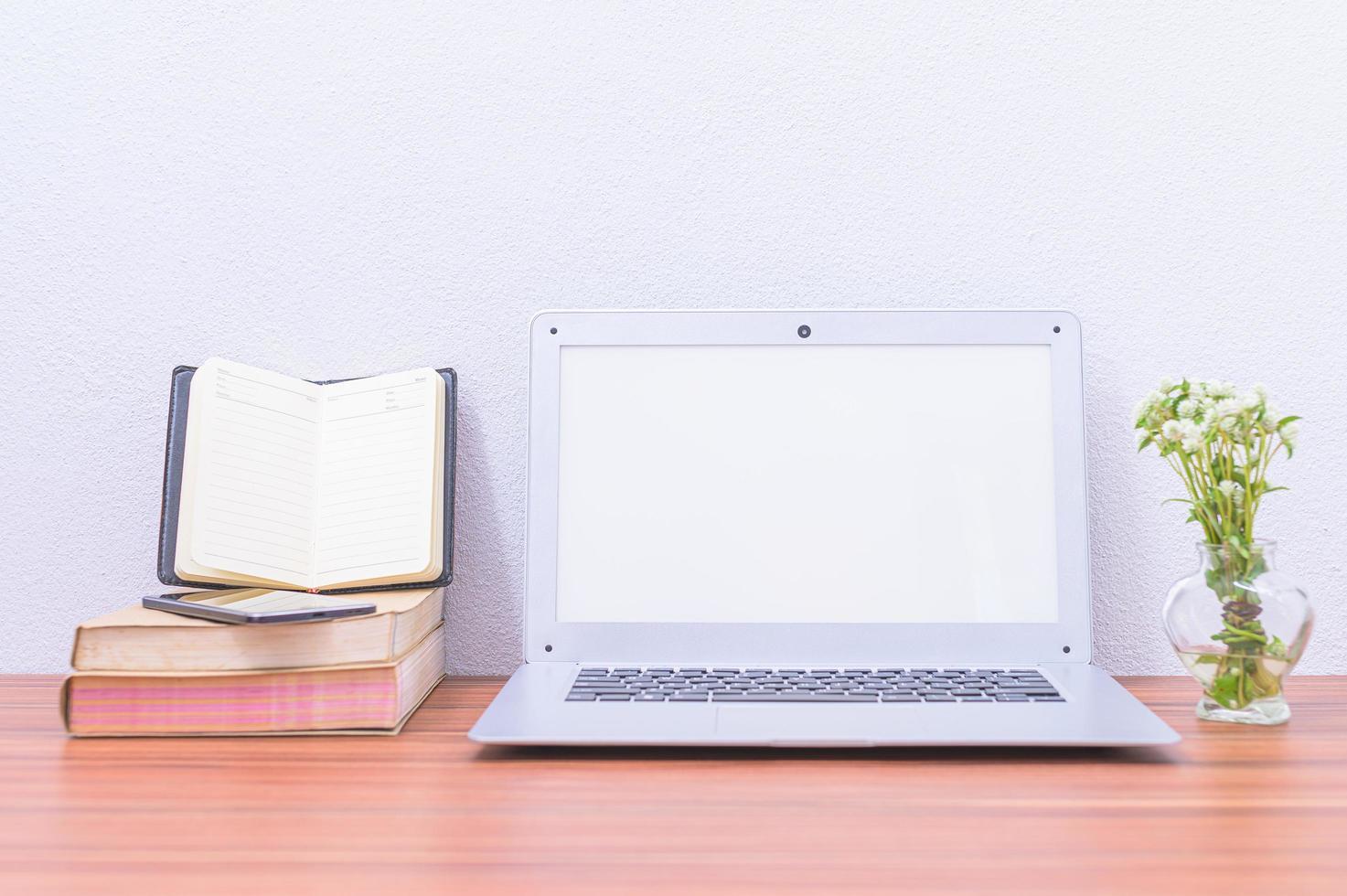 laptop e libri sulla scrivania foto