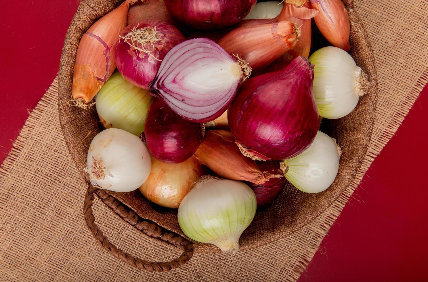 Vista dall'alto di diversi tipi di cipolla nel cesto su tela di sacco su sfondo rosso foto