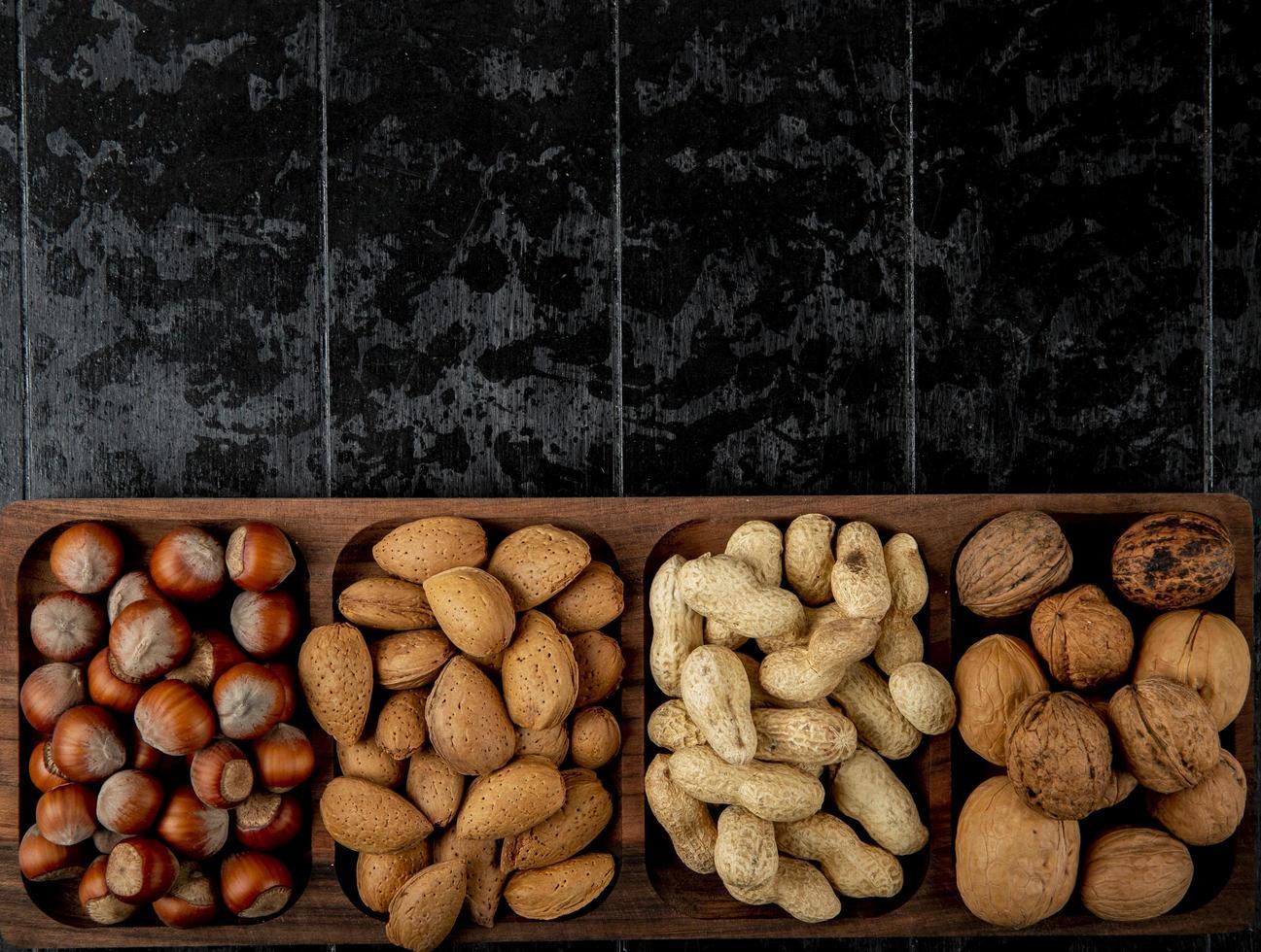 Vista dall'alto del mix di noci nocciole mandorle e arachidi in guscio su sfondo nero con copia spazio foto