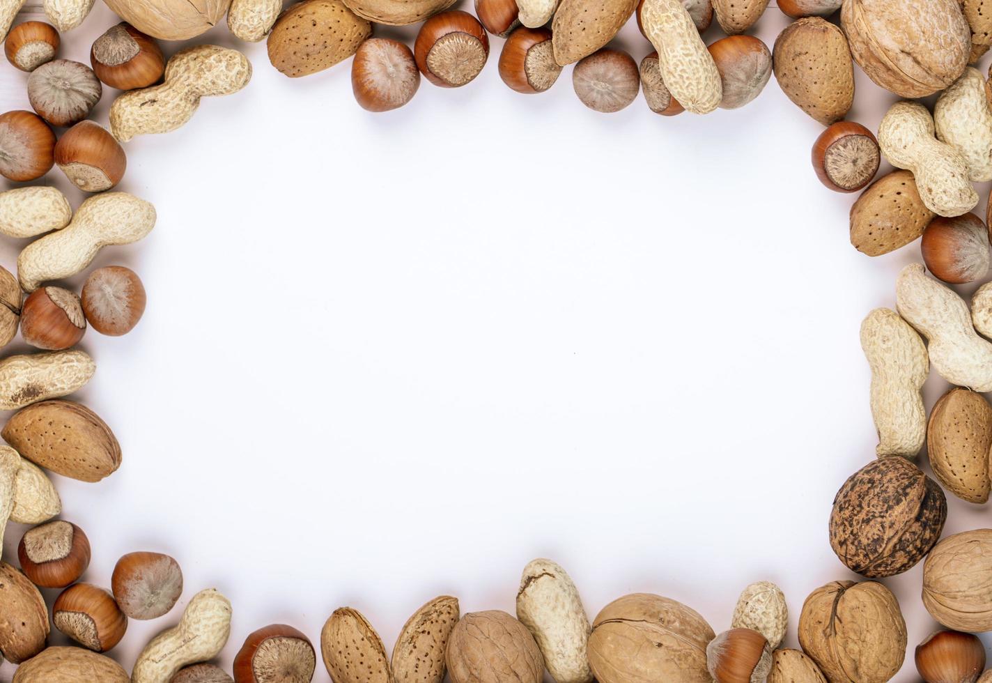 vista dall'alto di noci miste in guscio nocciole arachidi noci e mandorle su sfondo bianco con spazio di copia foto
