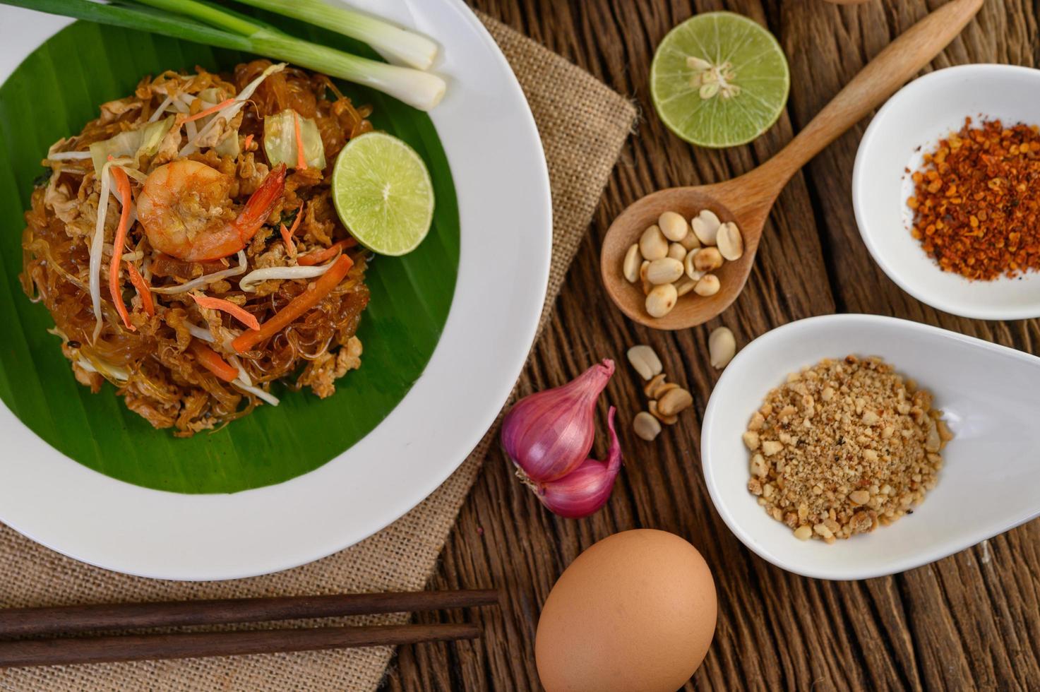 pad thai gamberetti in una ciotola con uova, cipollotto e condimenti foto