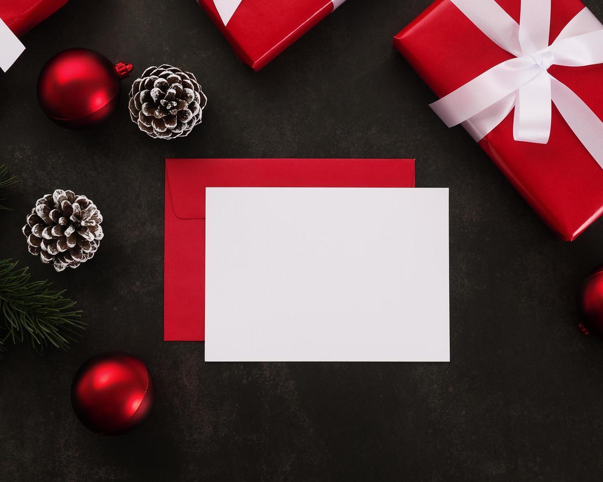 biglietto di auguri bianco vuoto e mockup di busta con decorazioni di regali di Natale su sfondo grunge foto