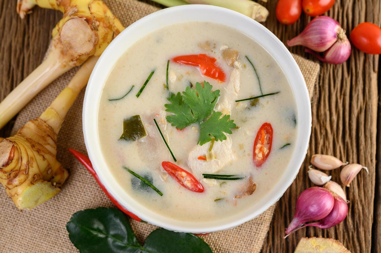 tom kha kai, zuppa di cocco tailandese sul bordo della cucina in legno foto