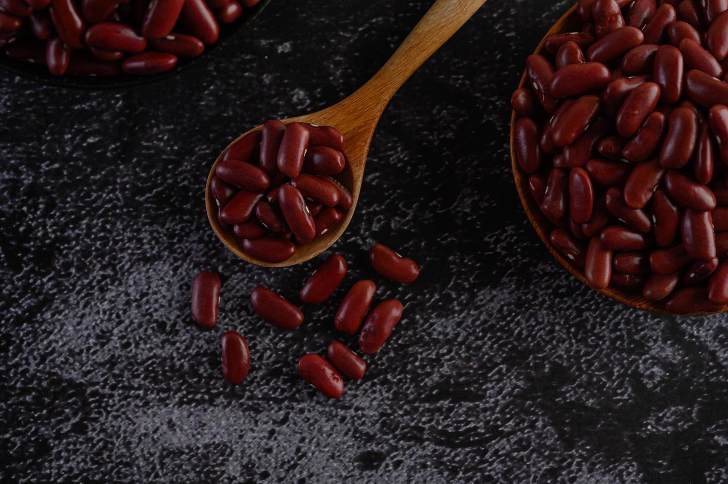 fagioli rossi in ciotole di legno sulla superficie della cucina nera foto