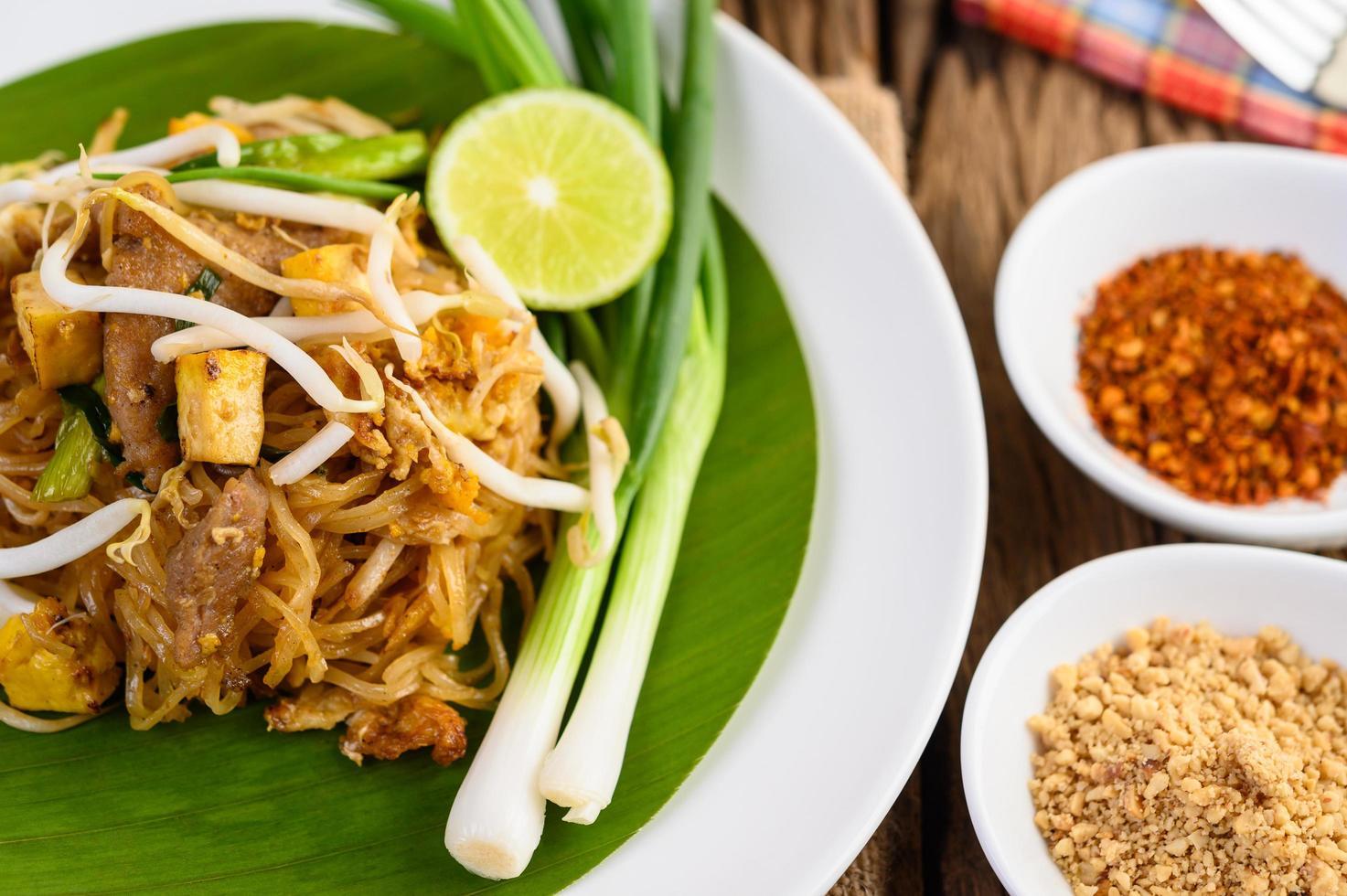 pad thai con limone, uova e condimento su un tavolo di legno foto