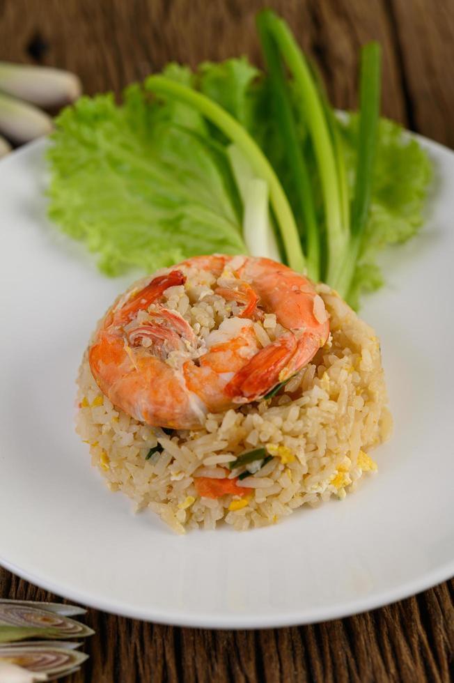 riso fritto con gamberetti su un piatto bianco foto