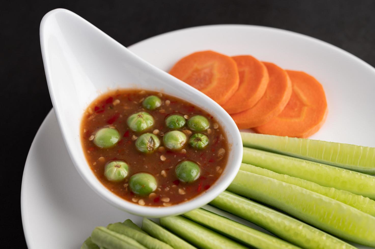 salsa di pasta di gamberetti in una ciotola con cetriolo, fagioli lunghi e carote foto