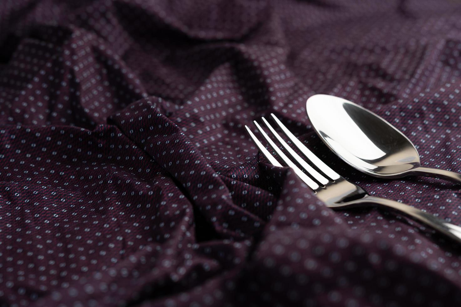 cucchiaio e forchetta posti su un panno spiegazzato foto