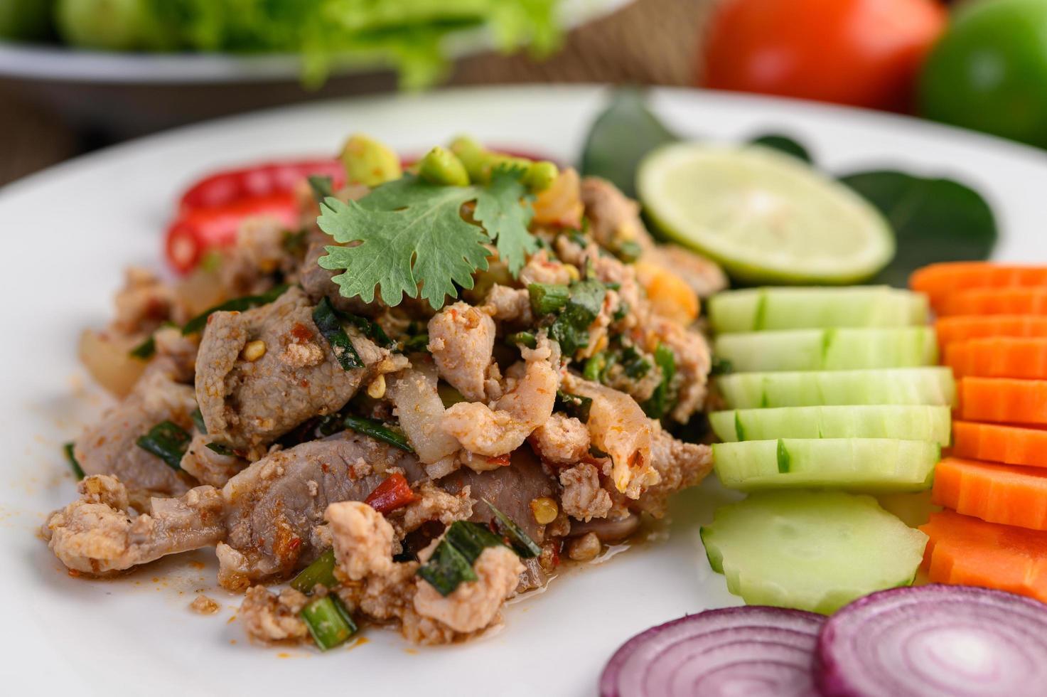 insalata di maiale macinata con spezie su un tavolo di legno foto