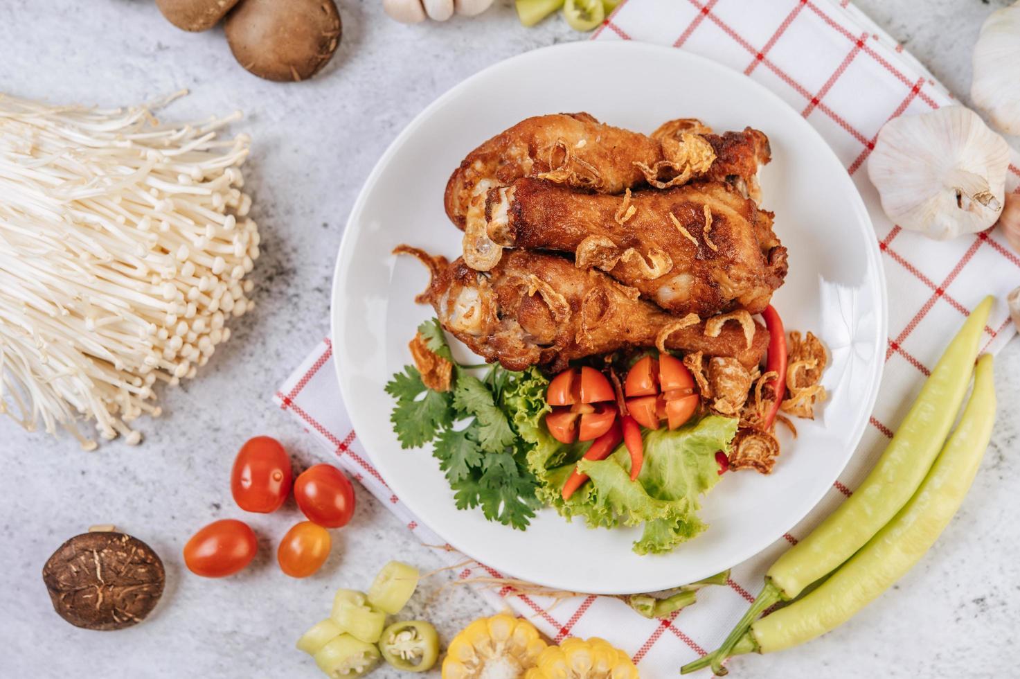 cosce di pollo fritte con pomodoro, peperoncino, cipolla fritta, lattuga, mais e funghi foto