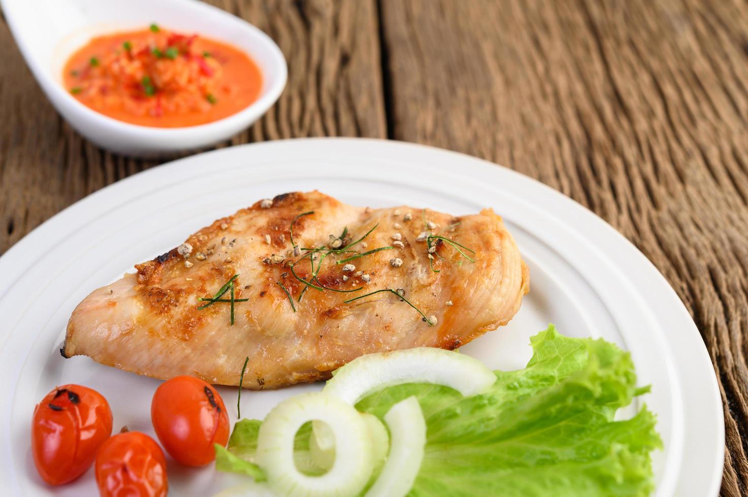 pollo alla griglia su un tavolo di legno con pomodori, insalata, cipolla e salsa di peperoncino foto