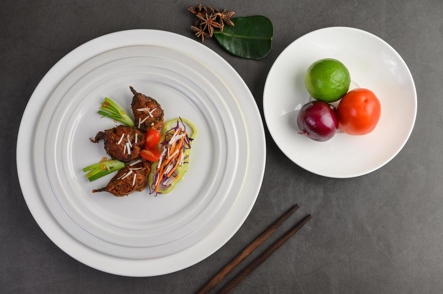 pesce gatto fritto piccante su un piatto bianco con le bacchette foto