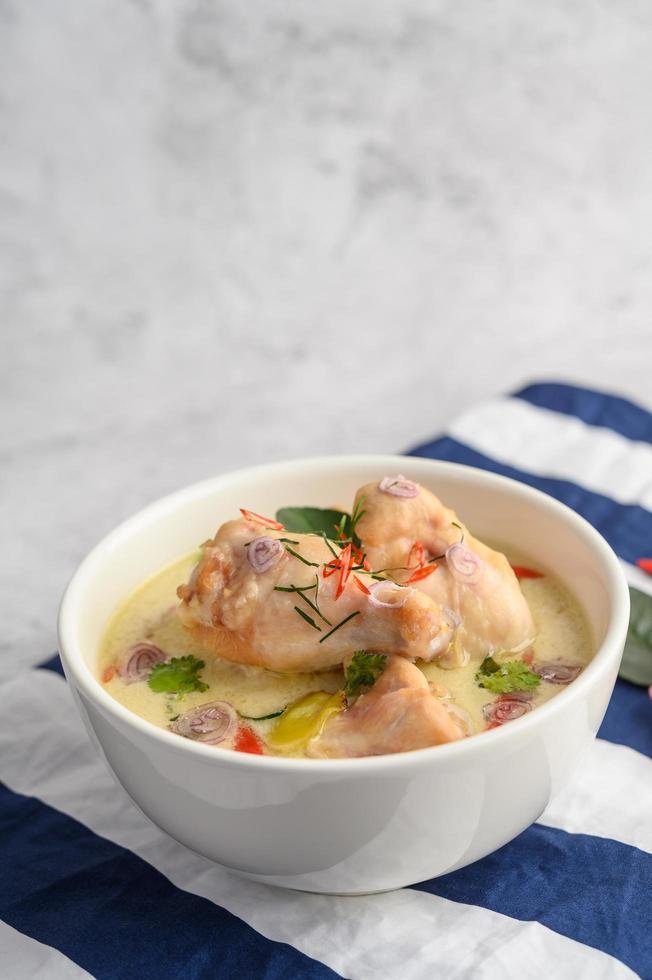 tom kha kai, zuppa di cocco tailandese su un panno a strisce blu foto