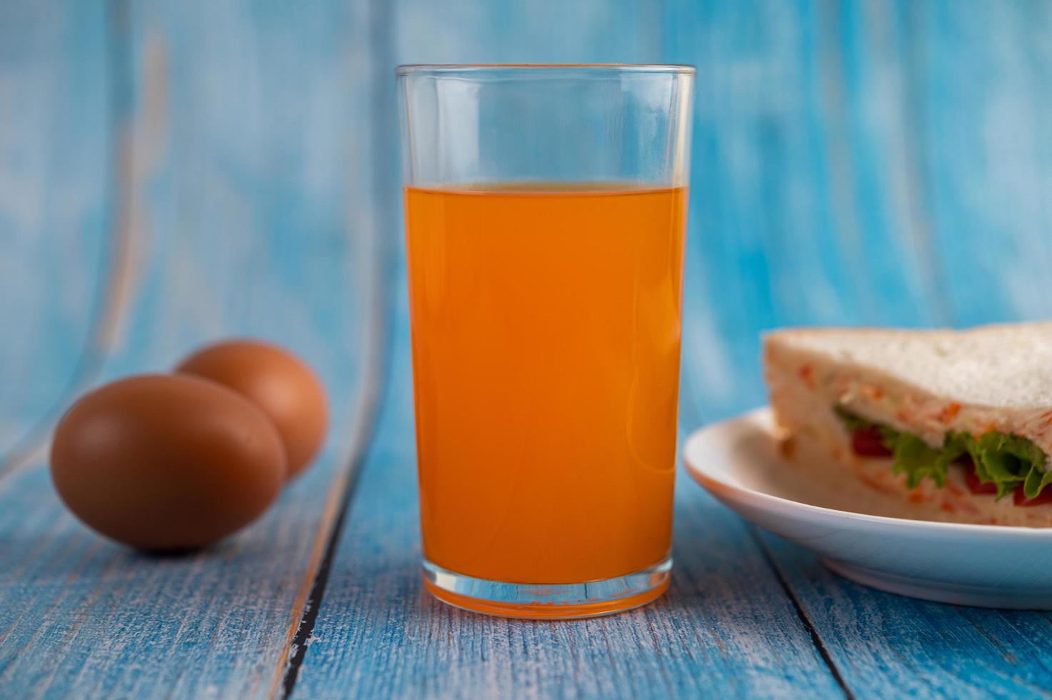 panini e succo d'arancia sulla tavola di legno blu foto