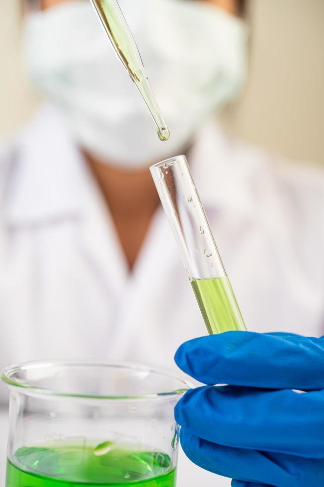 scienziato che indossa maschera e guanti che mostrano bicchieri con vaccini foto