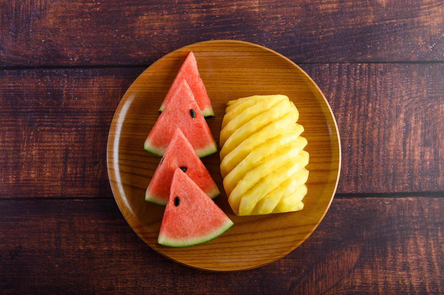 fette di anguria e ananas sul tavolo di legno scuro foto