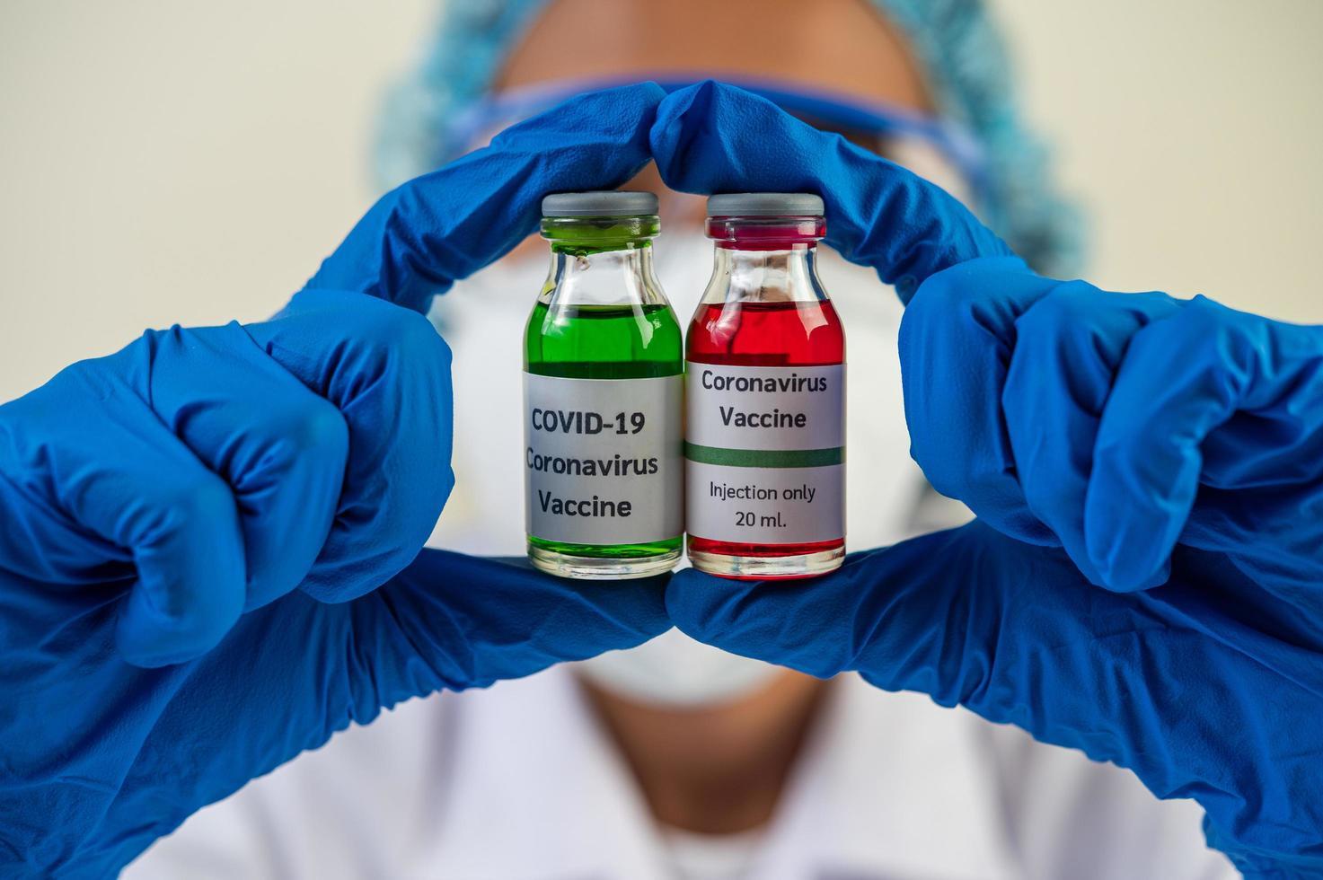scienziato che mostra fiale con vaccini per proteggersi da covid-19 foto