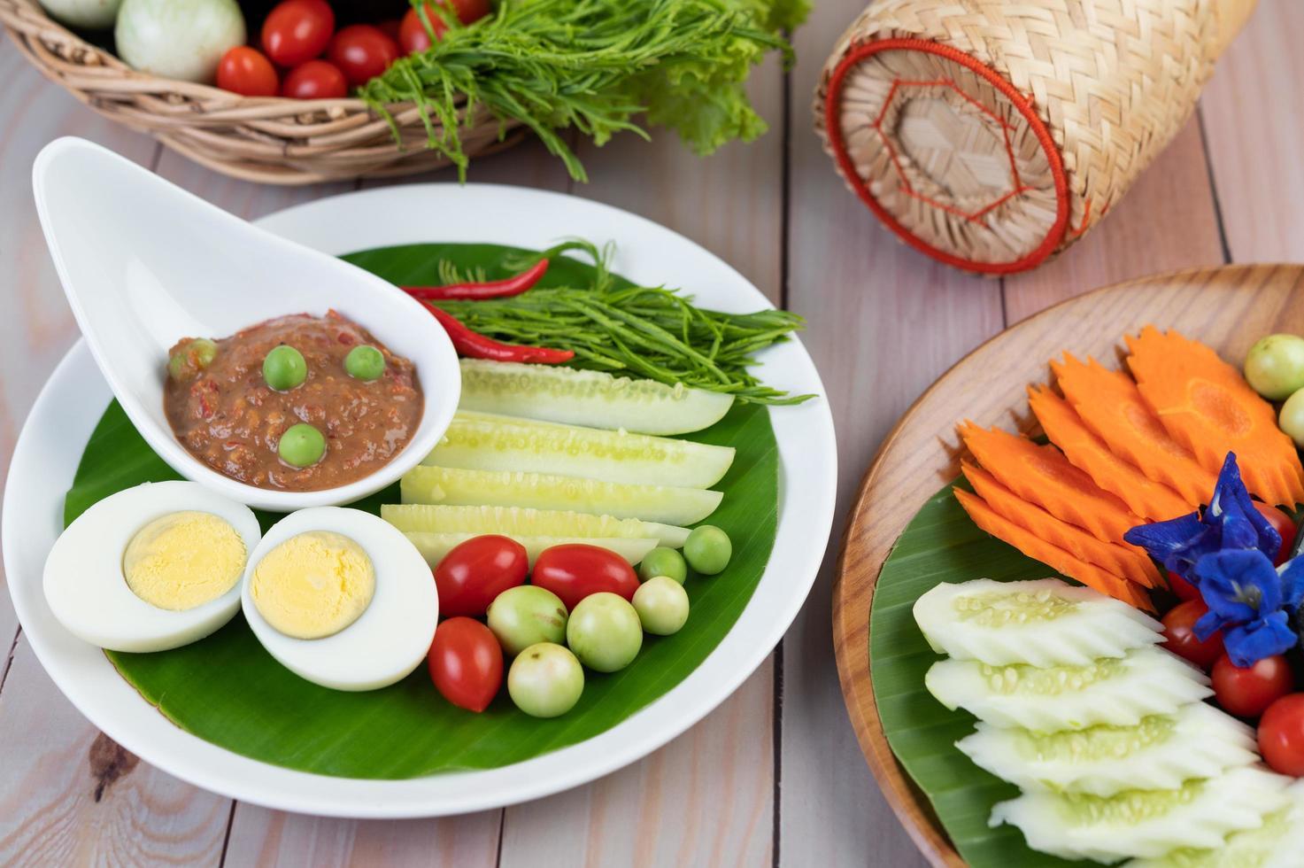 pasta di pasta di peperoncino in una ciotola con melanzane, carote, peperoncino e cetrioli in un cestino foto