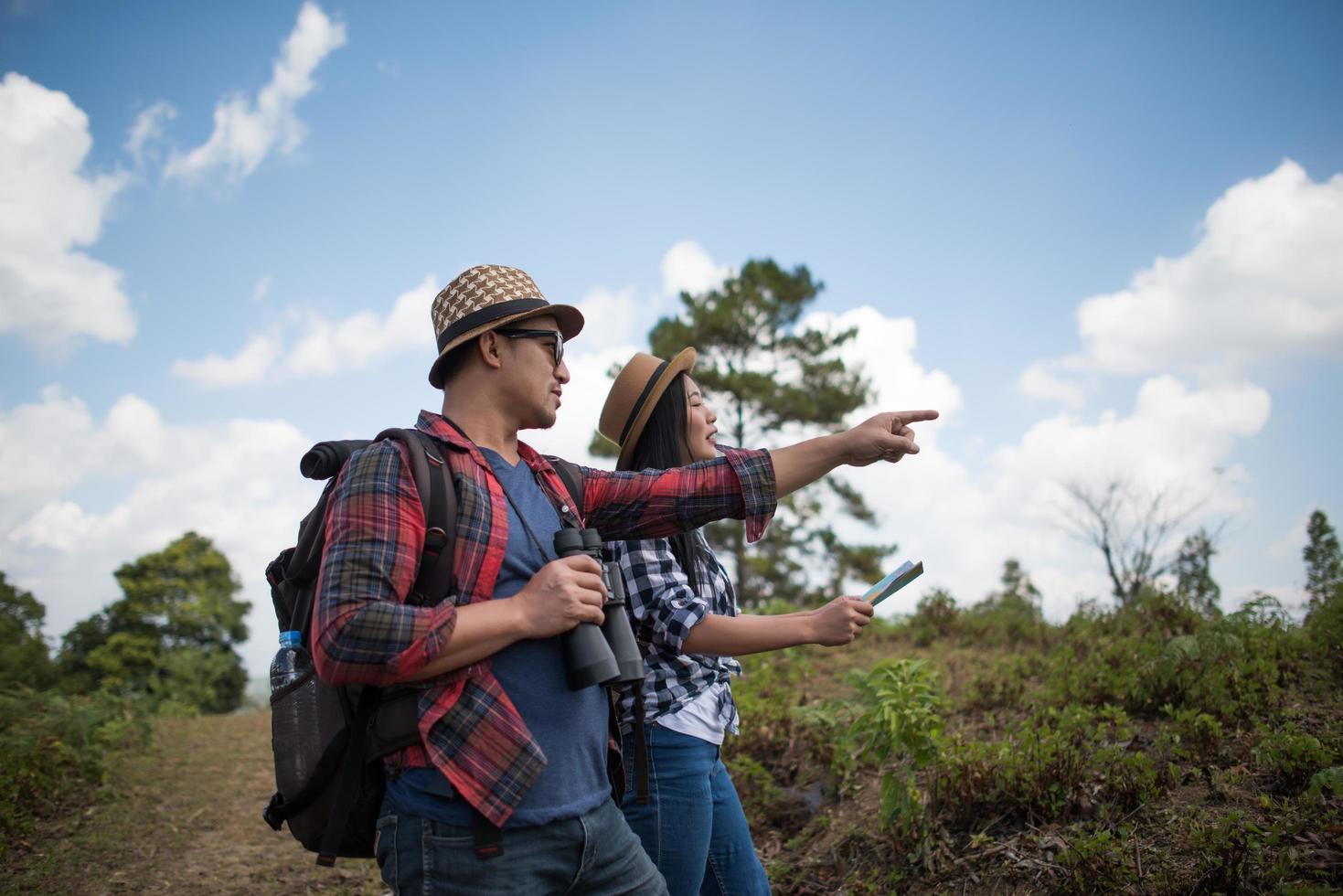 giovani coppie che camminano con gli zaini nella foresta foto