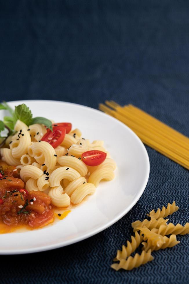 piatto di maccheroni con pomodoro, peperoncino, semi di peperone e basilico foto