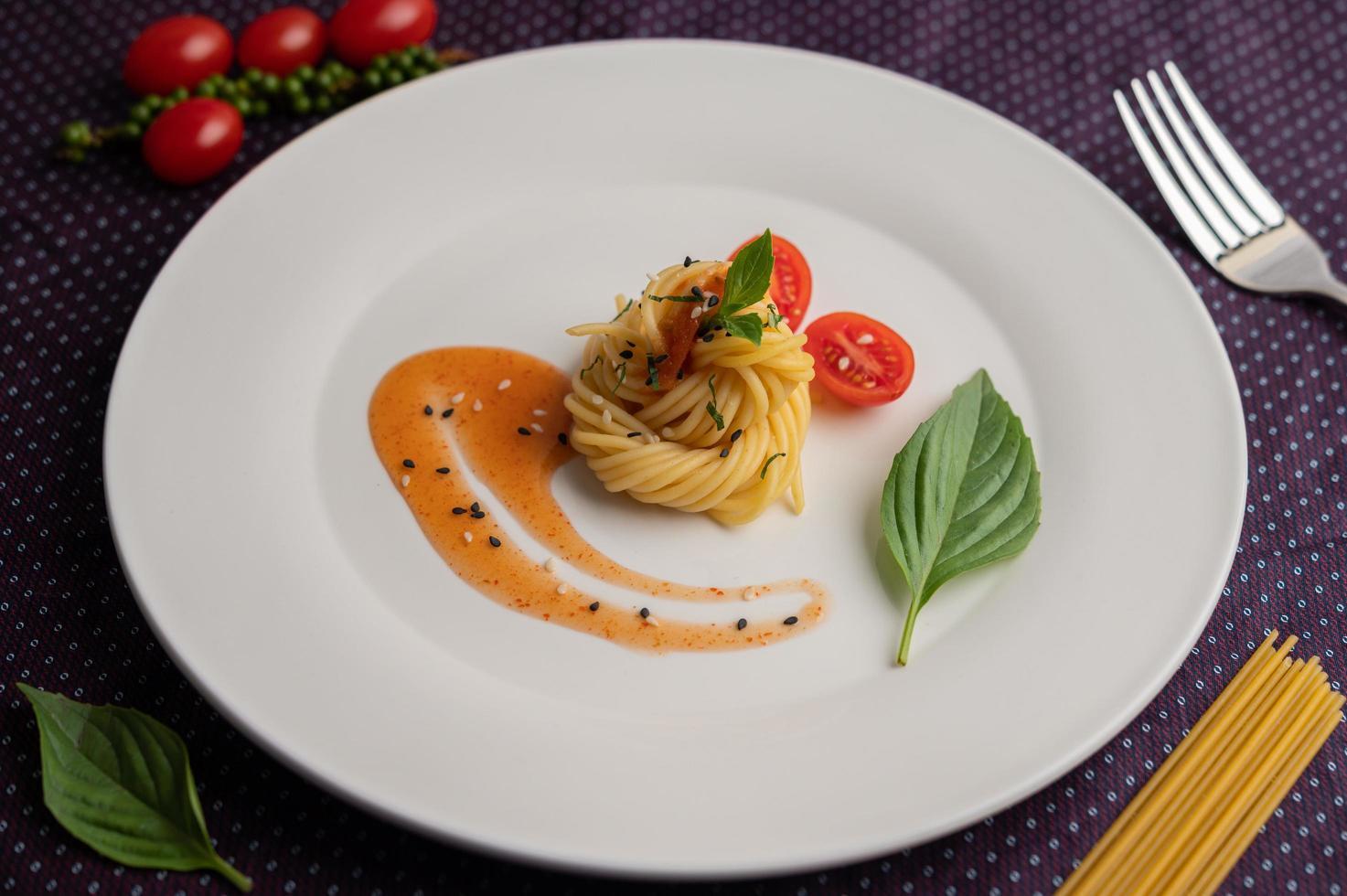 spaghetti gourmet splendidamente disposti su un piatto bianco foto