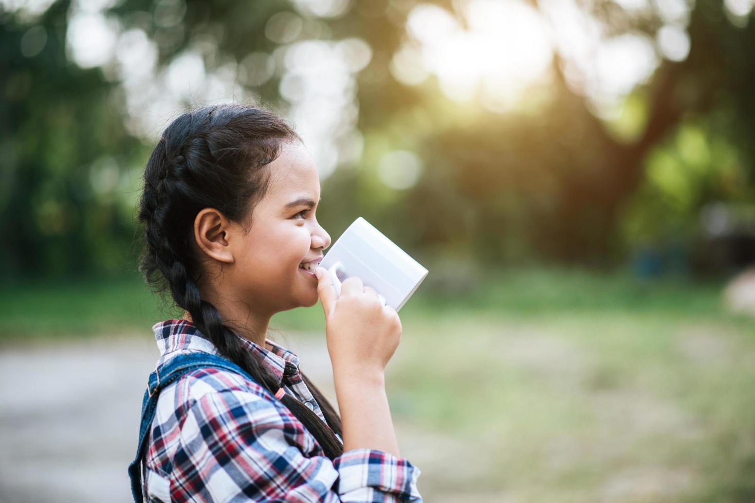 ragazza che beve latte dalla tazza foto