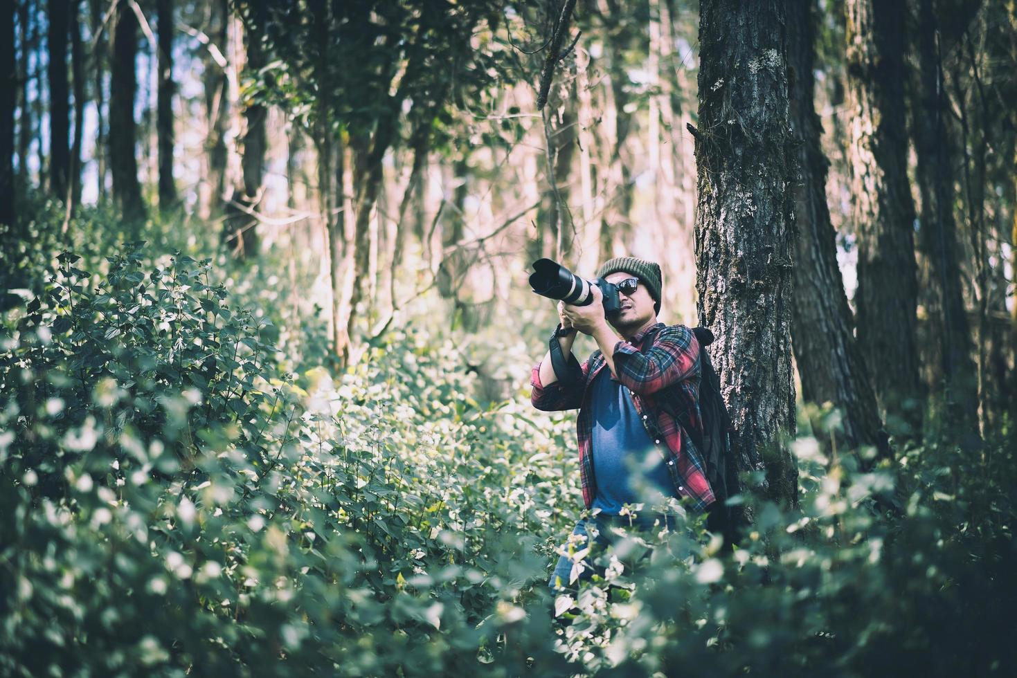 giovane fotografo che scatta foto nella foresta