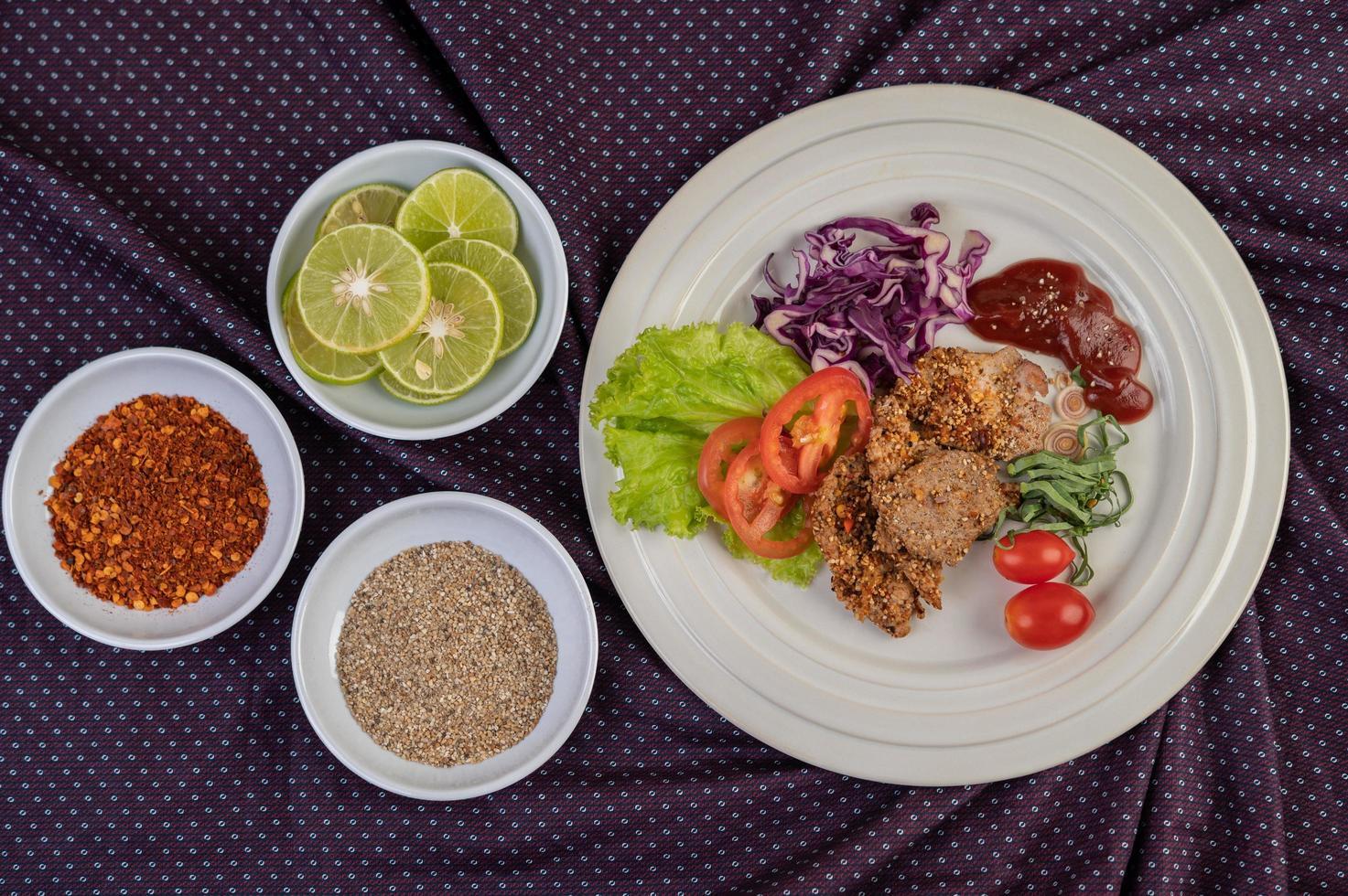 insalata di maiale placcato con peperoni, pomodoro, limone, lime, aglio e insalata foto