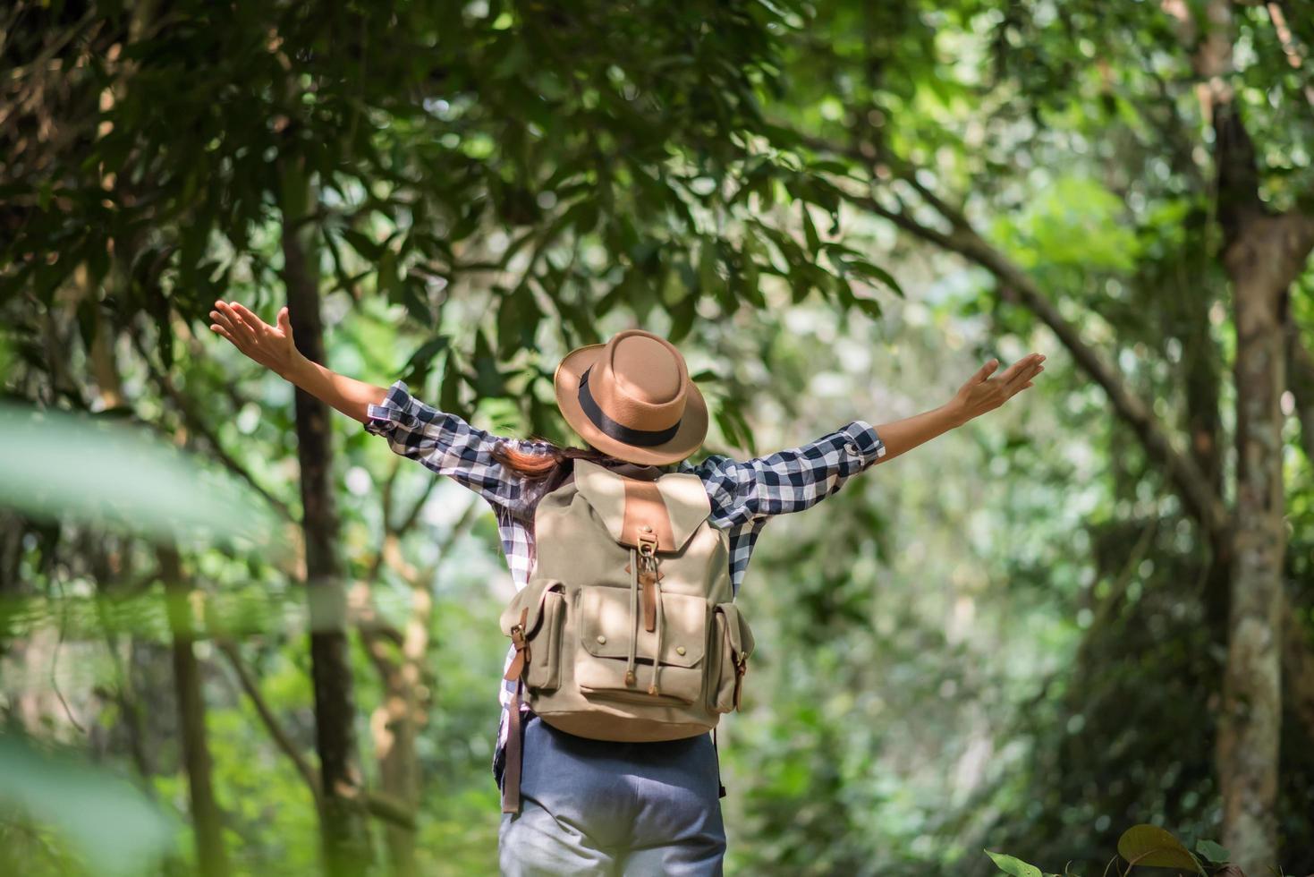 felice giovane donna alzando le braccia per salutare il sole nella foresta foto