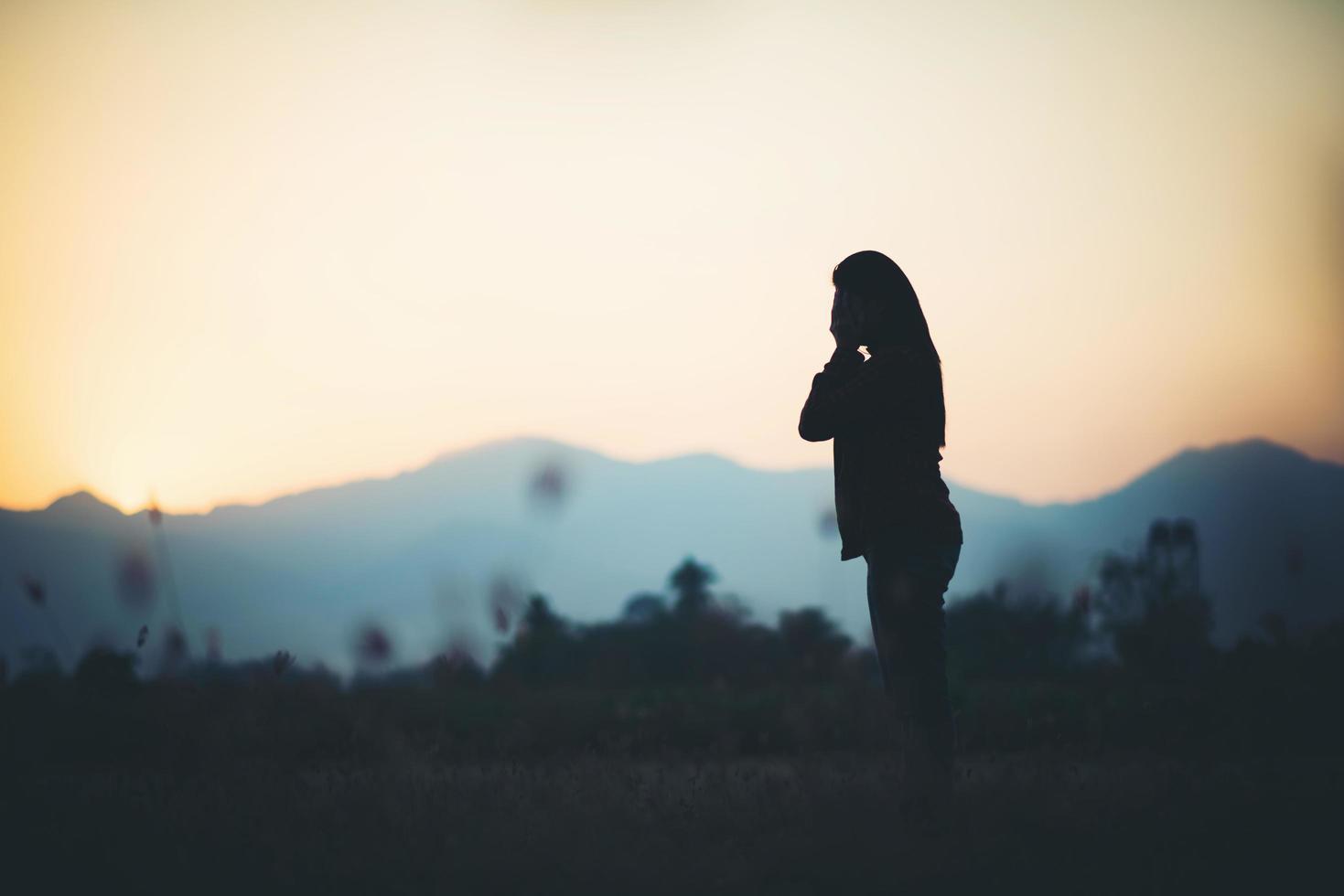 silhouette di donna su sfondo bellissimo tramonto foto