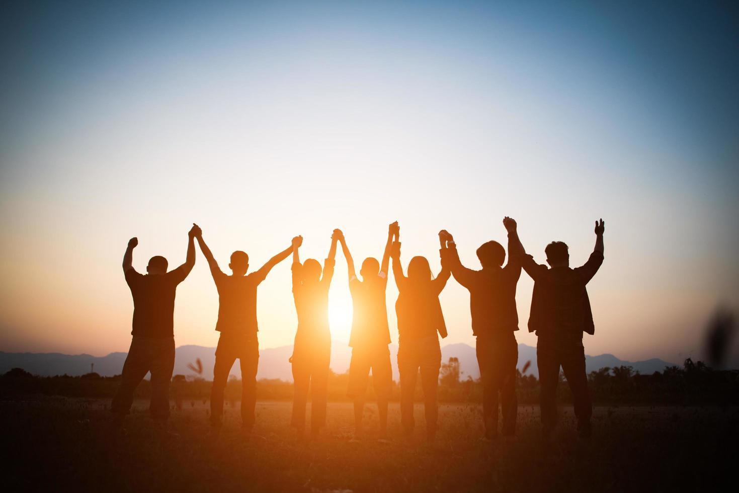 silhouette della squadra felice che fa le mani alte foto