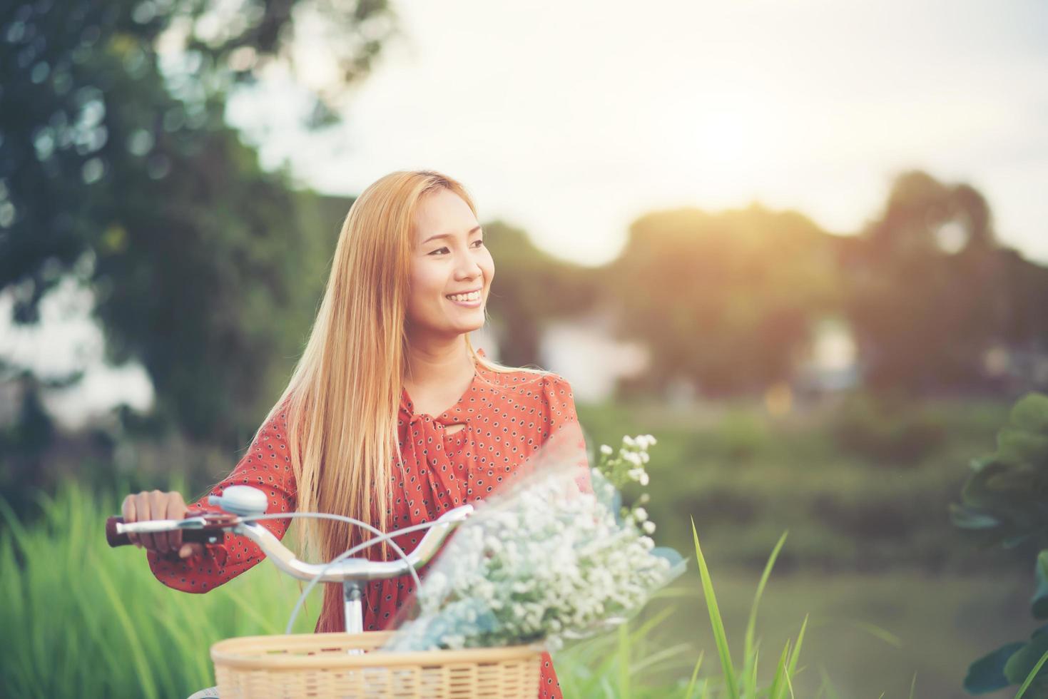 giovane donna asiatica in sella a una bicicletta in un parco foto