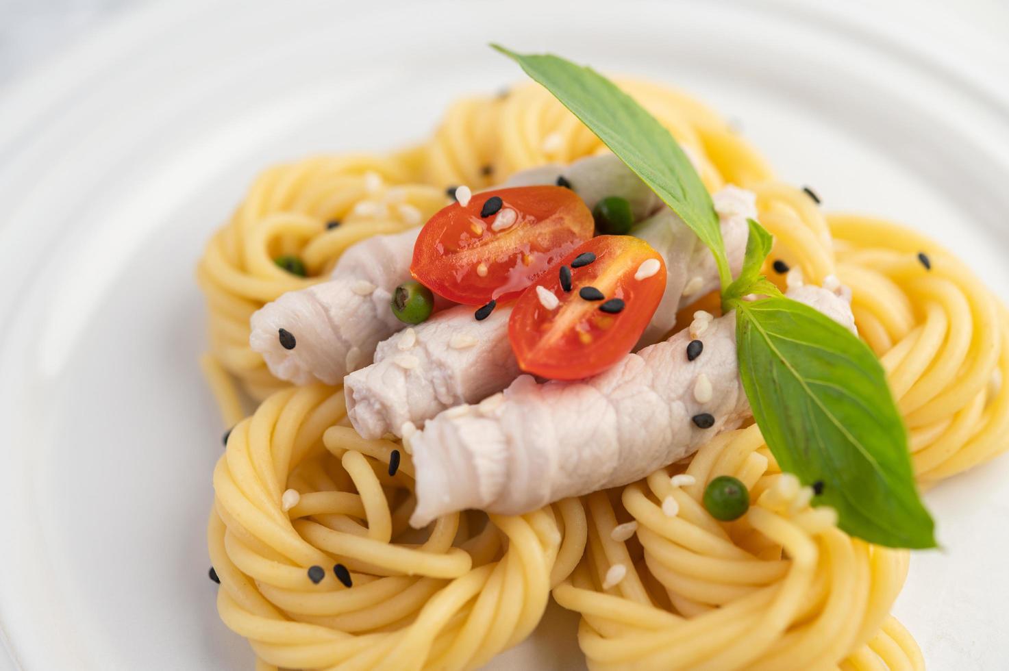 spaghetti e carne di maiale placcati disposti su un piatto bianco foto